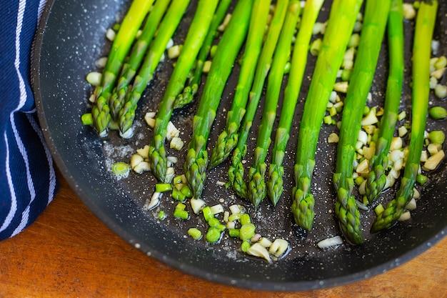 Lekkere groene asperges worden gebakken in een pan met knoflook, ernaast ligt een blauw gestreepte handdoek. detailopname.
