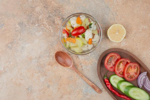 Lekkere groenten op glasplaat met houten plank van tomaat, komkommer en ui op marmer