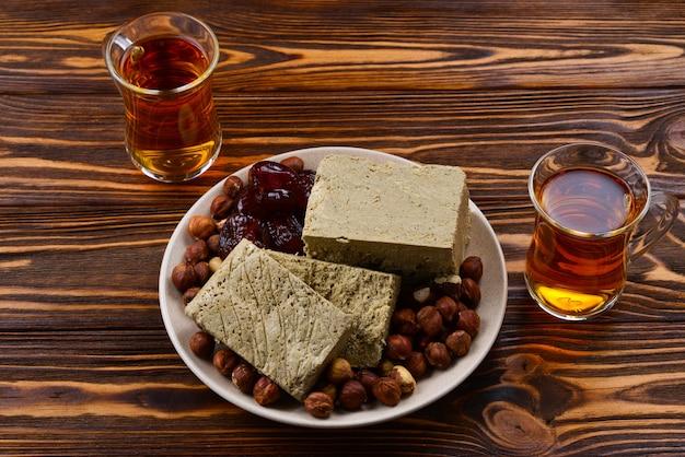 Lekkere halva met thee, noten, gedroogd fruit op houten tafel