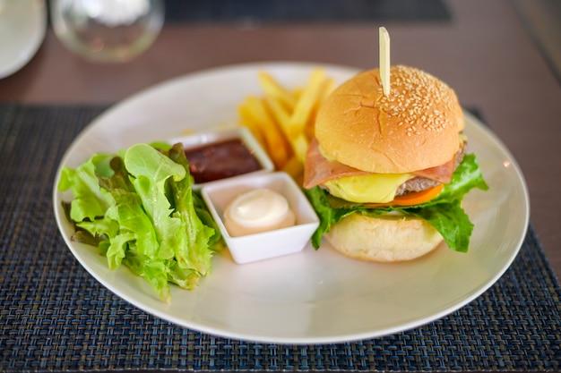 Lekkere hamburger met rundvlees geserveerd op een bord met sauzen en sla