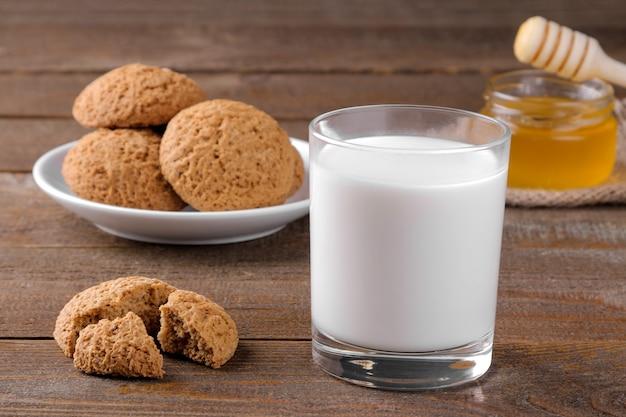 Lekkere havermoutkoekjes met honing en melk op een servet op een bruin houten tafel