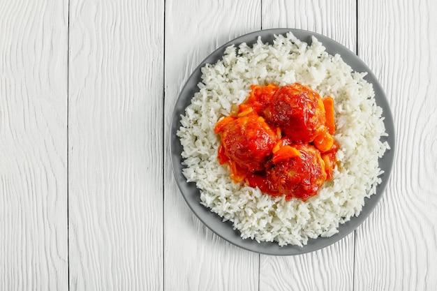 Lekkere hete kalkoen gehaktbal gestoofd in tomatensaus en groenten geserveerd met langkorrelige rijst