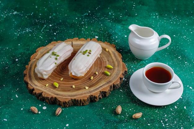 Lekkere huisgemaakte pistache-eclairs met witte chocolade.