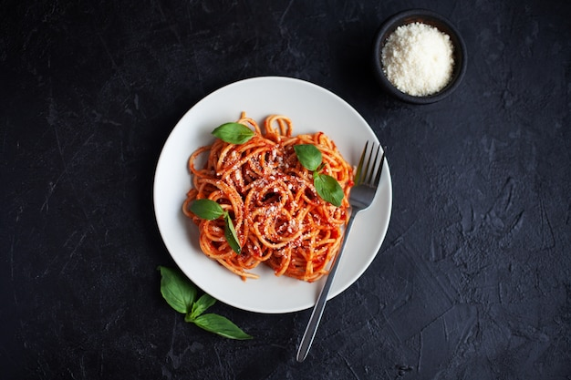 Lekkere italiaanse spaghetti met tomatensaus, kaas parmezaanse kaas en basilicum op plaat