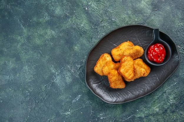 Lekkere kipnuggets en ketchup in zwarte plaat aan de linkerkant op een donkere ondergrond