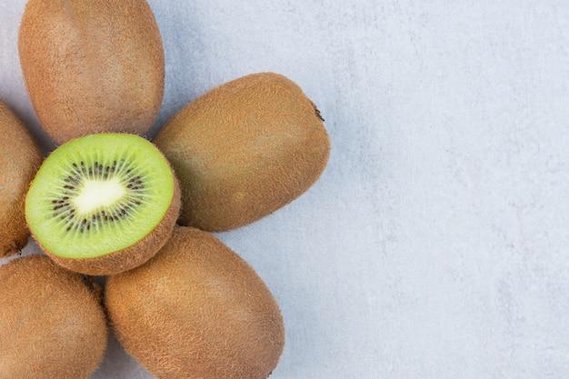 Lekkere kiwi's, heel en in plakjes, op de marmeren tafel.