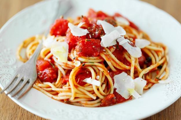 Lekkere klassieke italiaanse pasta met tomatensaus en kaas op plaat. detailopname.
