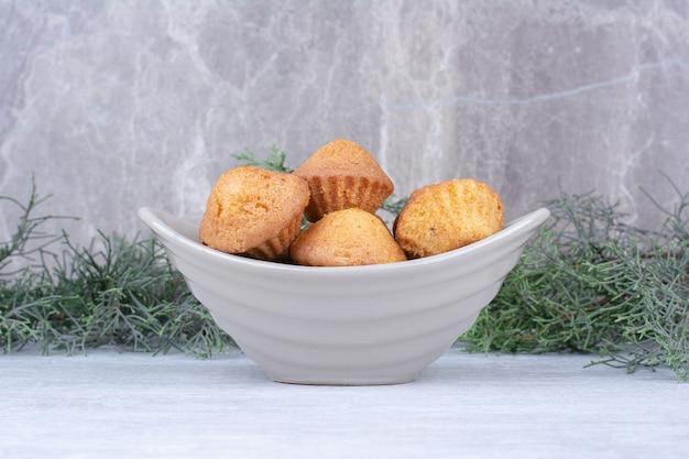 Lekkere kleine cakes in ceramische kom met dennentak