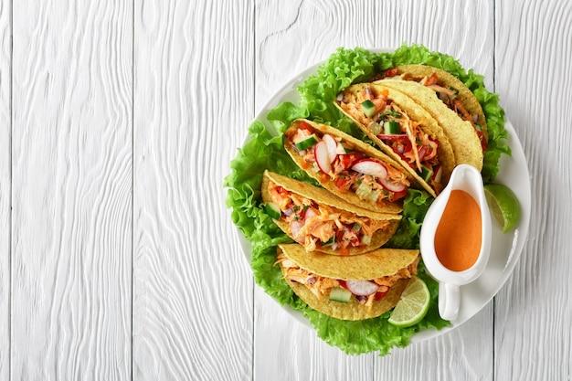 Lekkere knapperige maïstaco schelpen beladen met geraspte kipfilet, verse groenten en groenten met limoen en buffelsaus