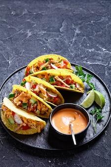 Lekkere knapperige maïstaco schelpen beladen met geraspte kipfilet, verse groenten en groenten op een zwarte plaat met limoen en buffelsaus