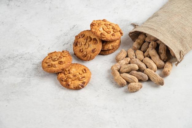 Lekkere koekjes met biologische honing en pinda's op marmeren tafel.