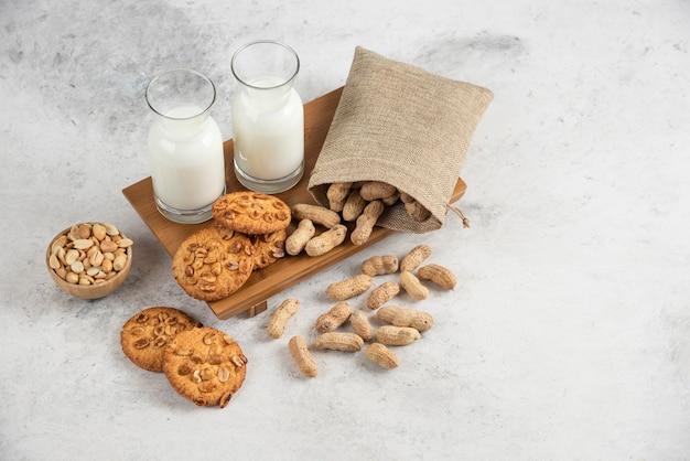 Lekkere koekjes met biologische pinda's en honing met glas melk op een houten bord.