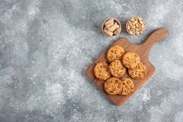 Lekkere koekjes met biologische pinda's en honing op een houten bord.
