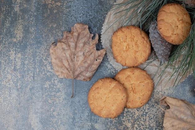 Lekkere koekjes met bladeren en dennenappel op marmeren tafel.