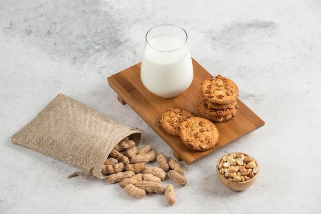Lekkere koekjes met honing en pinda's en glas melk op een houten bord.