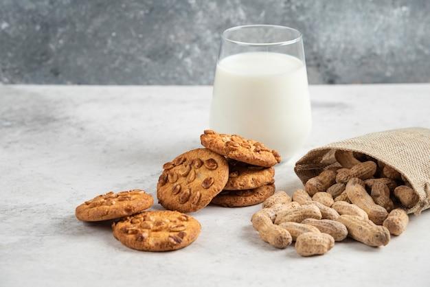 Lekkere koekjes met honing en pinda's en glas melk op marmeren tafel.