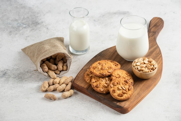Lekkere koekjes met honing, melk en pinda's op een houten bord.