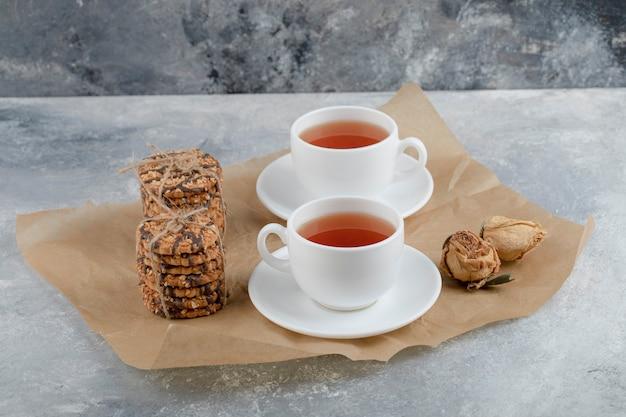 Lekkere koekjes met zaden en chocolade met kopje thee op marmer.