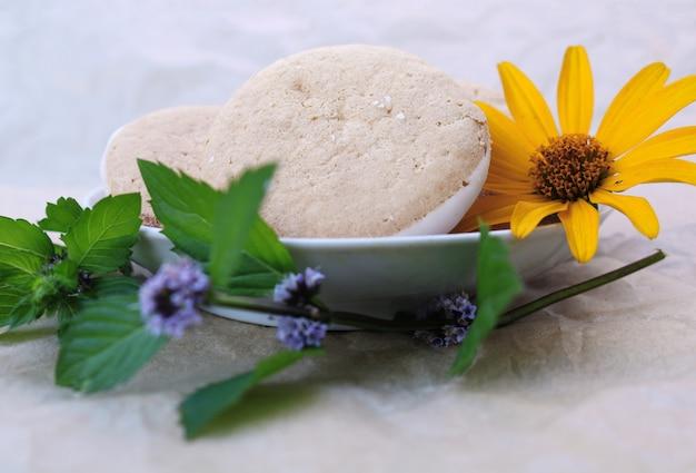 Lekkere koekjes op een schotel met blaadjes munt en gele bloem
