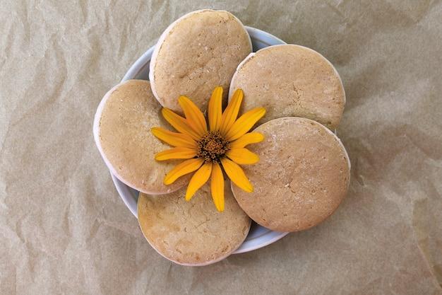 Lekkere koekjes op een schoteltje met gele bloem