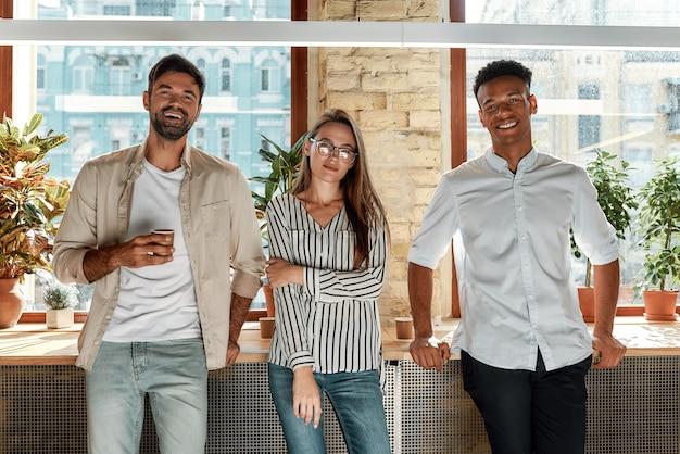 Lekkere koffie drie vrolijke collega's in vrijetijdskleding die naar de camera kijken terwijl ze in de moderne staan