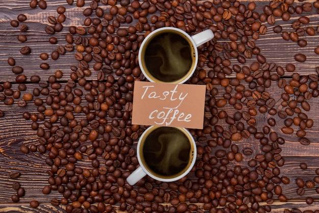Lekkere koffie kopjes op koffiebonen. houten tafeloppervlak op oppervlak.