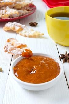 Lekkere krokante gefrituurde koekjes in poedersuiker met thee en jam bij het ontbijt