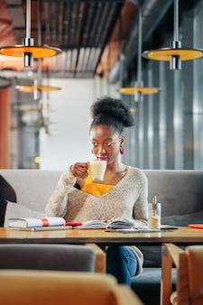 Lekkere latte drinken curly internationale mooie student die lekkere latte drinkt in de cafetaria