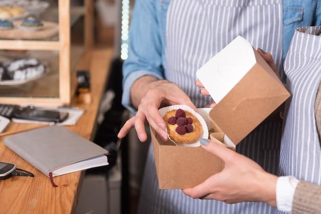 Lekkere maaltijd. jonge mooie obers die cake in de doos houden terwijl ze achter de bar staan.