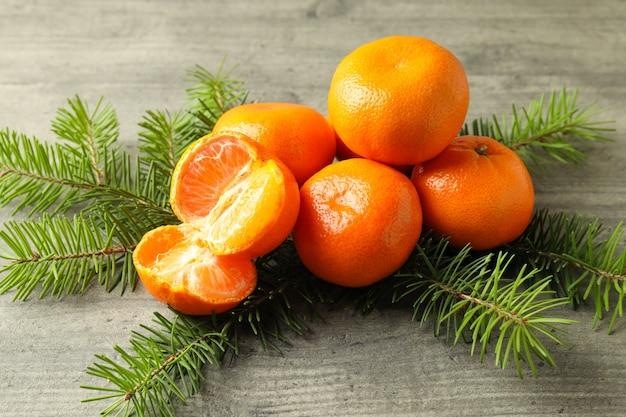 Lekkere mandarijnen en sparren takken op grijze getextureerde tafel
