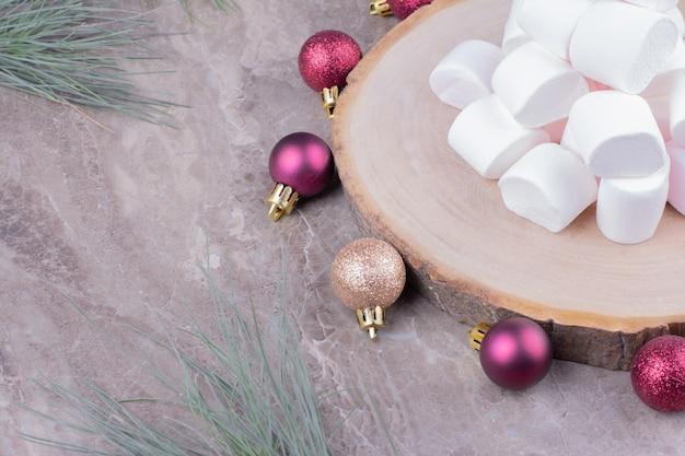 Lekkere marshmallows op een houten bord met rond eikenboomballen