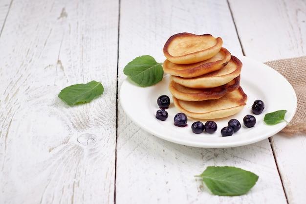 Lekkere mooie pannenkoeken met bosbessen en bosbessenyoghurt op een lichte houten tafel met muntblaadjes.