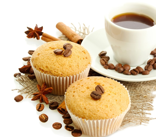 Lekkere muffin taarten met kruiden op jute en kopje koffie, geïsoleerd op wit