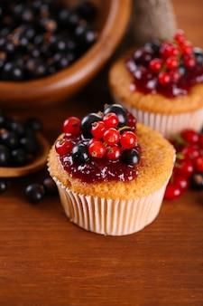 Lekkere muffins met bessen op houten tafel