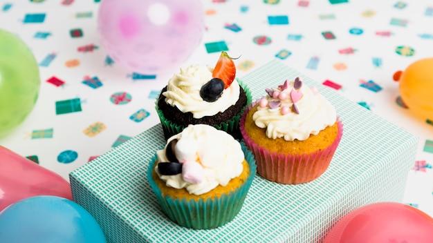 Lekkere muffins op huidige doos in de buurt van ballonnen