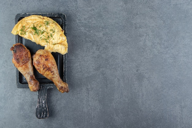 Lekkere omelet en kippenpoten op zwart bord.