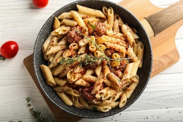 Lekkere pasta met vlees en kruiden in pan op tafel