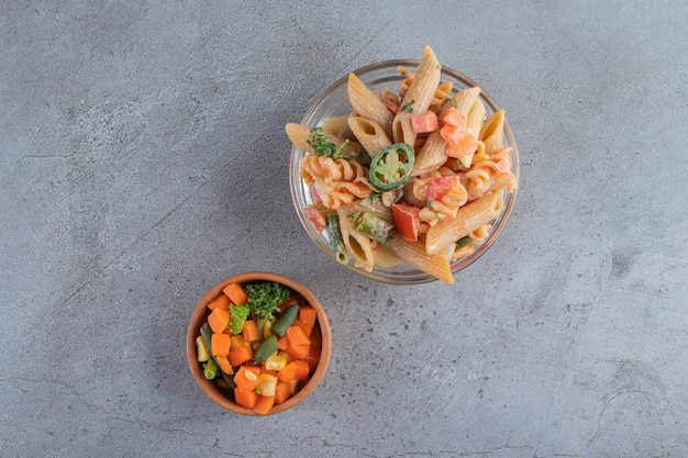 Lekkere penne pasta en frisse salade op stenen achtergrond.