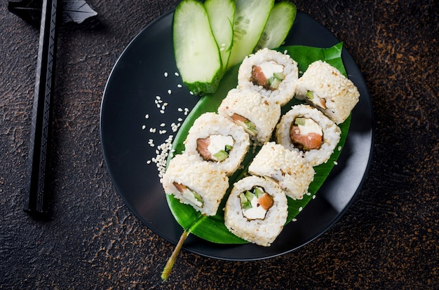 Lekkere philadelphia roll sushi met zalm en roomkaas in sesam op zwarte plaat met sojasaus, gember, wasabi en eetstokjes op donkere tafel. sushimenu. bezorgservice japans aziatisch eten.