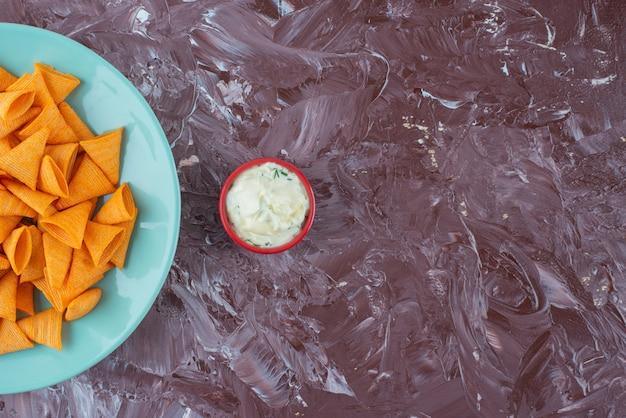Lekkere pittige chips op een bord naast yoghurt op het marmeren oppervlak