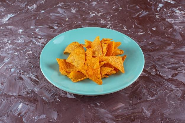 Lekkere pittige chips op een bord, op de marmeren tafel.