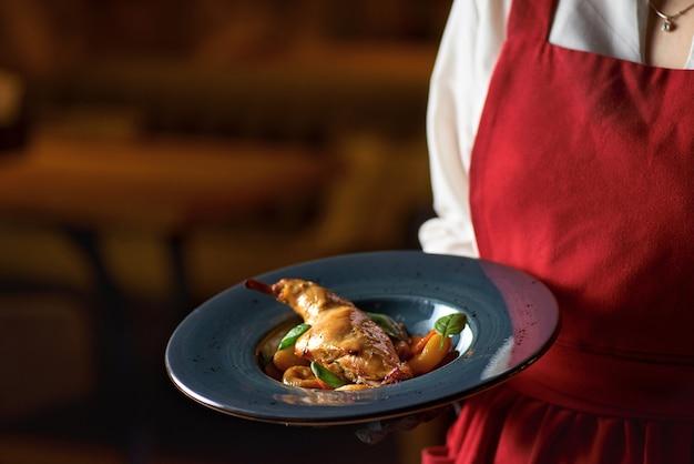 Lekkere pittige konijnenstoofpot in tomatensaus met witte wijn en kruiden close-up op tafel, serveren in een restaurant