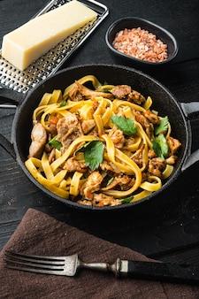 Lekkere pittige konijnenstoofpot met pasta tagliatelle of pappardelle set, in gietijzeren pan of pot, op zwarte houten tafel