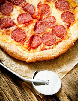 Lekkere pizza en mes op een oud papier. op een houten achtergrond.