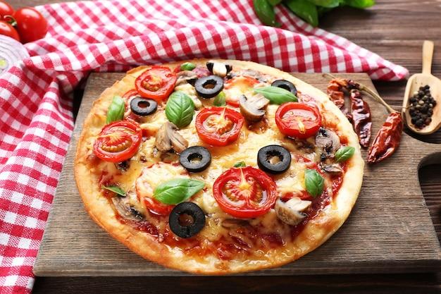Lekkere pizza met groenten en basilicum op tafel close-up