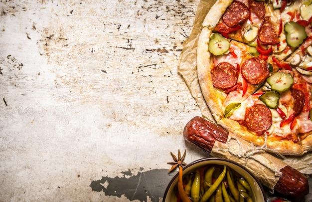 Lekkere pizza met pepperoni en tomatensaus. op rustieke achtergrond. vrije ruimte voor tekst. bovenaanzicht