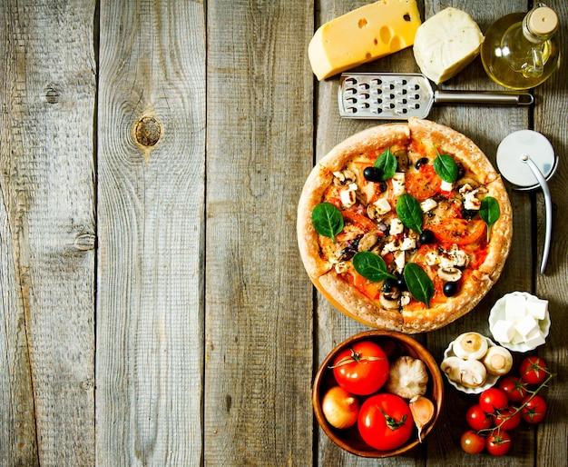 Lekkere pizza op een houten bord. veggie een pizza met ingridients.