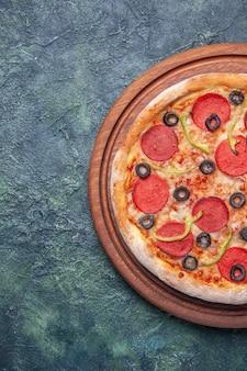Lekkere pizza op houten snijplank aan de linkerkant op geïsoleerde donkere ondergrond met vrije ruimte