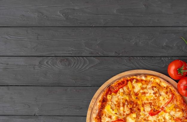 Lekkere pizza op zwarte houten bovenaanzicht