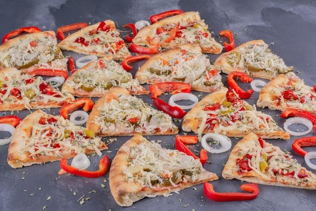 Lekkere pizzaplakken op blauw met uienringen en peper.